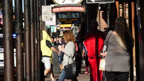 New Orleans LA Oct 2017 : People crossing a sidewalk zooming out to show the street scene and metal poles on Bourbon St New Orleans Louisiana