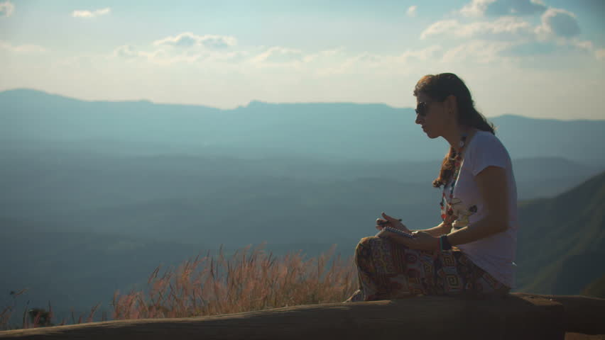 Woman thinking and writing above the moutains