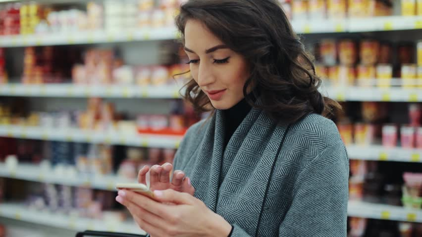 Happy young woman use phone in supermarket smiling look at camera shopping internet buying technology hypermarket shop mall smartphone shopper grocery market girl food customer slow motion