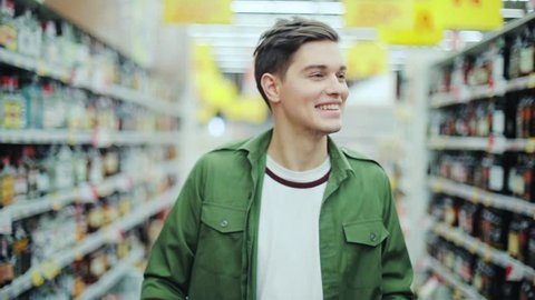 Attractive man walk with shopping cart at the supermarket happy hypermarket hand food shop store customer grocery handsome indoor lifestyle male market buyer guy product shopper slow motion smile