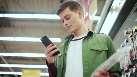 man stand use phone hold ham in the supermarket shopping technology adult caucasian male store young attractive department mobile handsome business buyer close up portrait slow motion