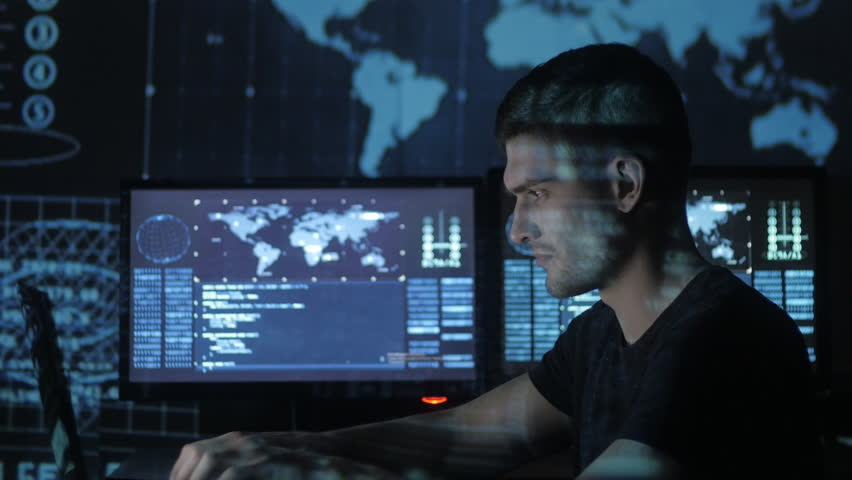 Male hacker programmer working at computer while blue code characters reflect on his face in cyber security center filled with display screens. | Shutterstock HD Video #1008776771