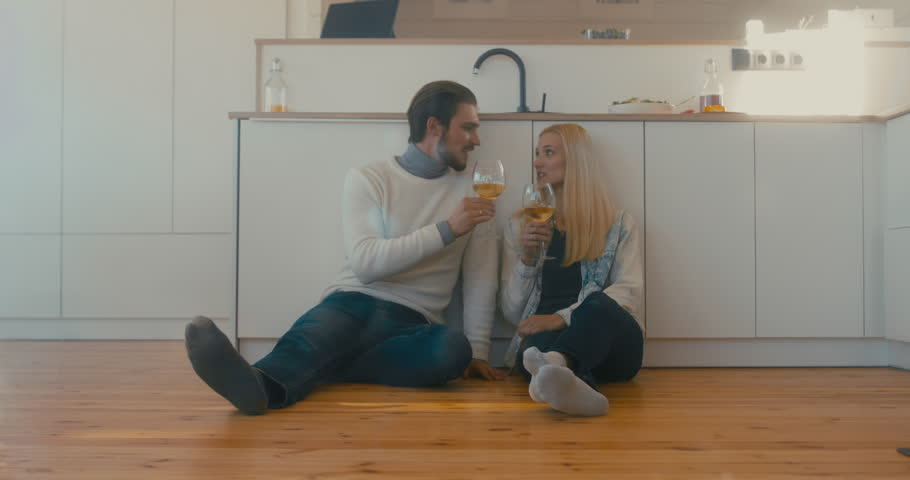 Young adult beautiful Caucasian couple celebrating something at home, drinking wine on the floor. 4K UHD   Shutterstock HD Video #1008781841