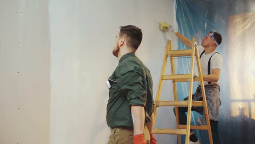 Handsome young builder decides to have a break from the refreshment process, hilariously dances, juggles the paint roller, his co-worker applauses him. Party hard, positive mood, having fun. Slow