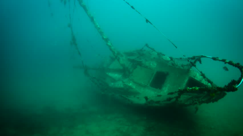 Old underwater sunken sailboat shipwreck covered in corals and fish. Scuba diver is exploring and filming mysterious sunken ship or boat. Mediterranean, Adriatic sea, Fiesa, Slovenia.