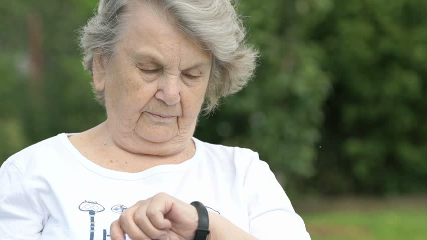 Black wristband. Mature elderly woman dressed in white t-shirt looks at the results of physical activity using a wristband fitness tracker. Positive person.