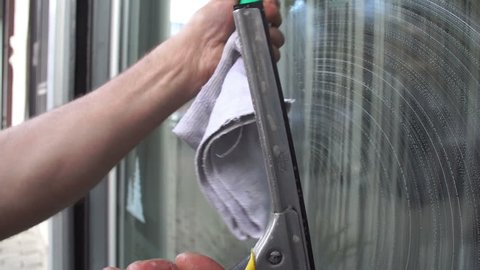 Cleaning the window. A young man cleans and polishes windows with a sponge