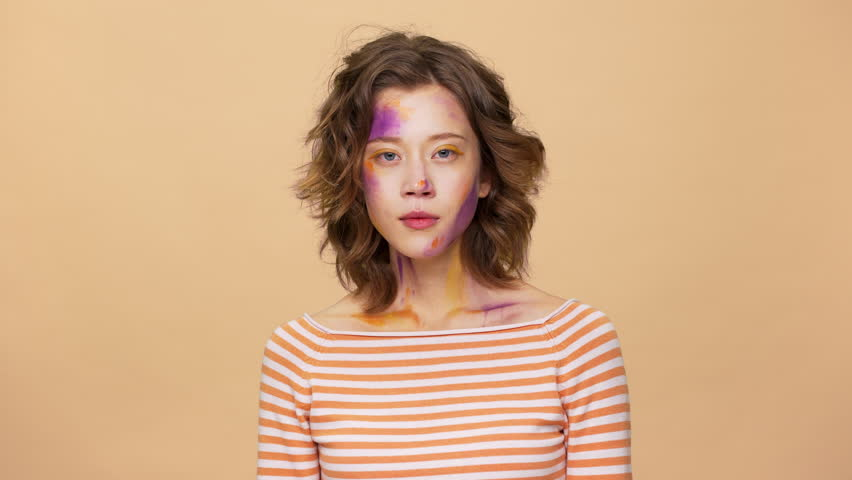 Portrait of caucasian brunette woman with art spots on face expressions mood swings from happiness and laughter to irritation, isolated over beige background. Concept of emotions