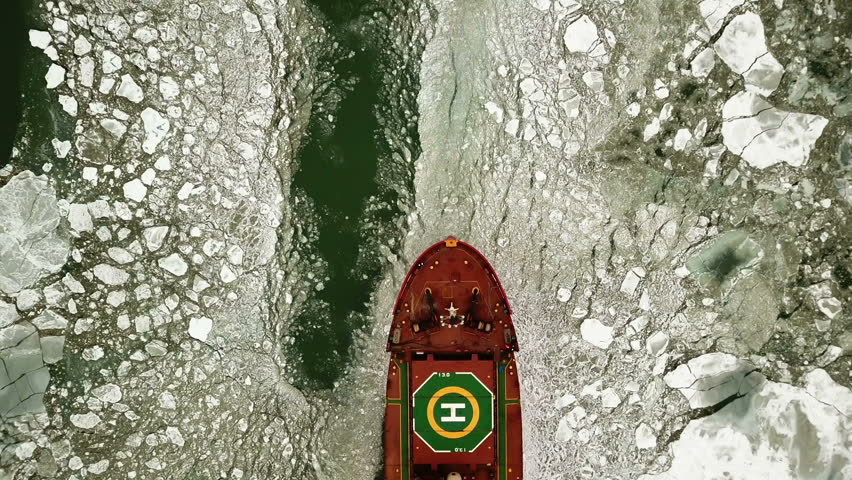 Aerial view. The big ship sails through the sea ice in the winter, close-up