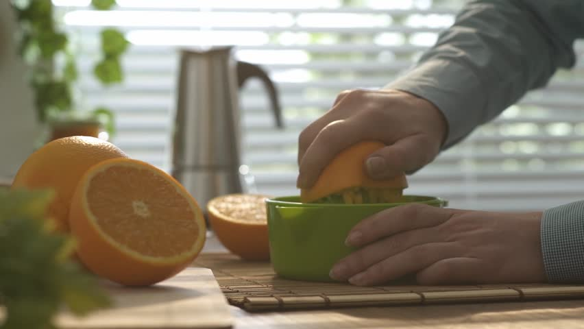 Woman preparing an healthy fresh orange juice for morning breakfast in the kitchen, she is squeezing an orange with a manual juicer