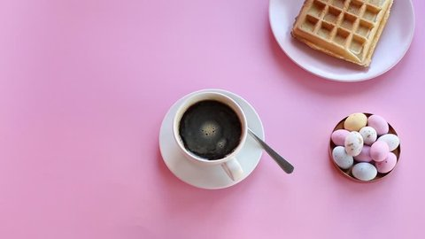 Cinemagraph : sweet breakfast and a cup of coffee. Waffle, chocolates on pink background.