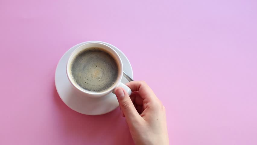 Cinemagraph : hand from right side holds a cup of stirring coffee on pink background.