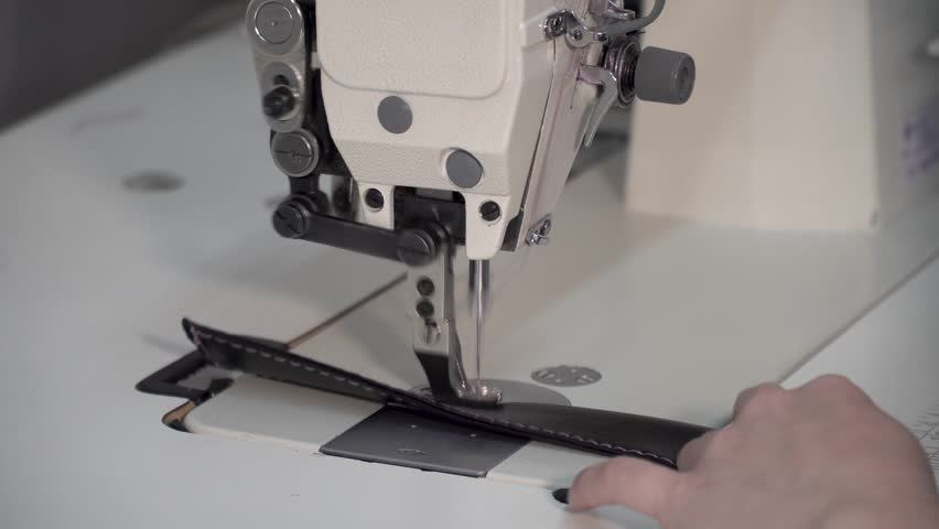 Seamstress works on a sewing machine, sews fabric, makes a line, close-up | Shutterstock HD Video #1008849941