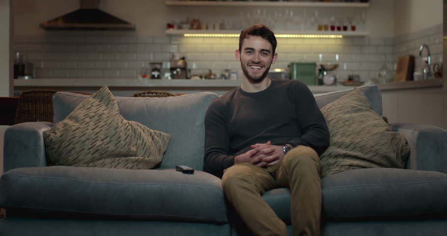 Young man relaxing on a couch watching tv, smiling and laughing. | Shutterstock HD Video #1008851171