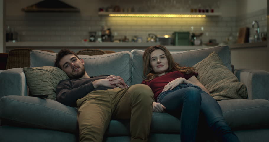 Relaxed couple slump on the couch in a cozy living room watching tv.