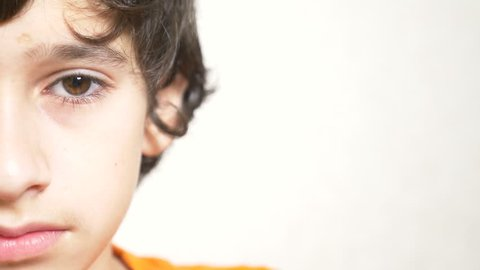 A young boy looks at the camera . 4k. close-up, half face, copy space. Slow motion