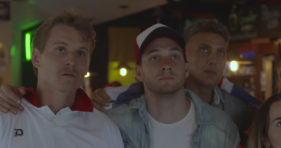 British football fans reacting to defeat while watching match in sports bar, slow motion