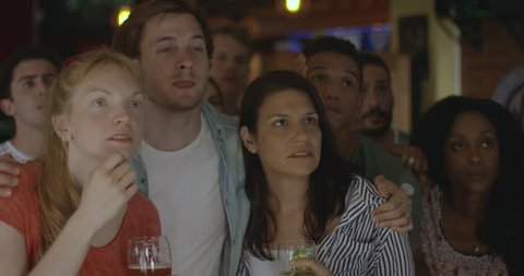 Sports enthusiasts reacting to defeat while watching televised match in bar, slow motion