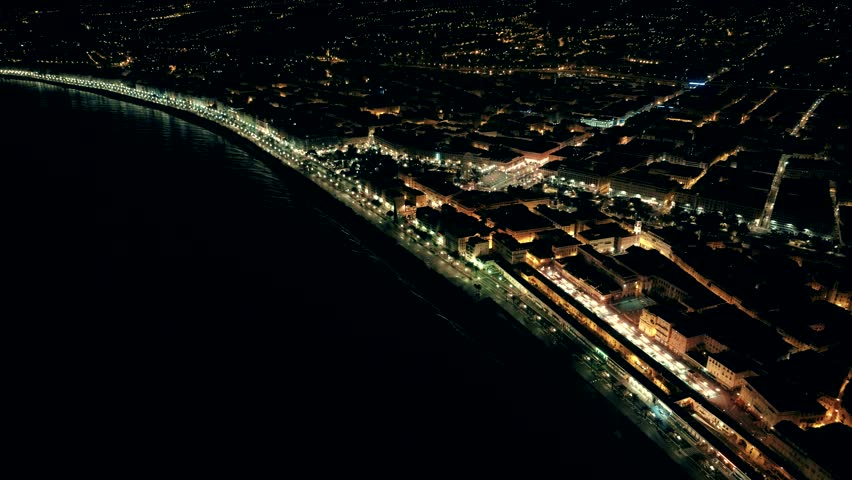 Night aerial view of illuminated Nice town in France. Flight over promenade.