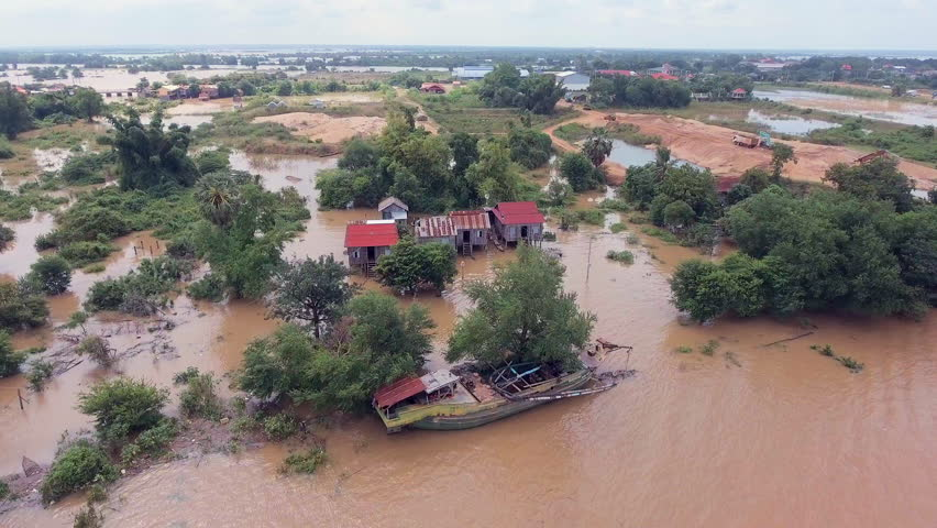 Aerial drone shot ; fly over flooding along the river inundated rural houses and agricultural fields