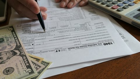 A Man Reads Income Tax Return Refund Forms 1040. Calculator, Dollars, Mobile Phone On The Table