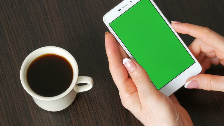 Female hands with beautiful French manicure take white smartphone with Green Screen near white cup of coffee. Using Smartphone,Holding Smartphone with Green Screen #1008930581