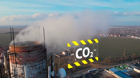 Aerial view of an industrial pipe pollutes the air next to people living in the city. Create a Greenhouse effect. 3D Hologram Warning CO2.