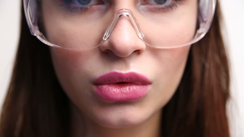 face of a sexy woman in construction glasses close-up. the girl is erotically chewing gum.