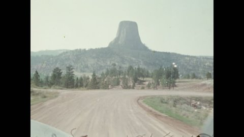 "1950s: Car drives down road. Rock formations. Ranger stands next to sign reading ""DEVILS TOWER NATIONAL MONUMENT."" Man walks past."