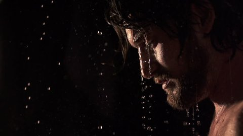 emotional slow motion of man opening his eyes in the rain, medium shot