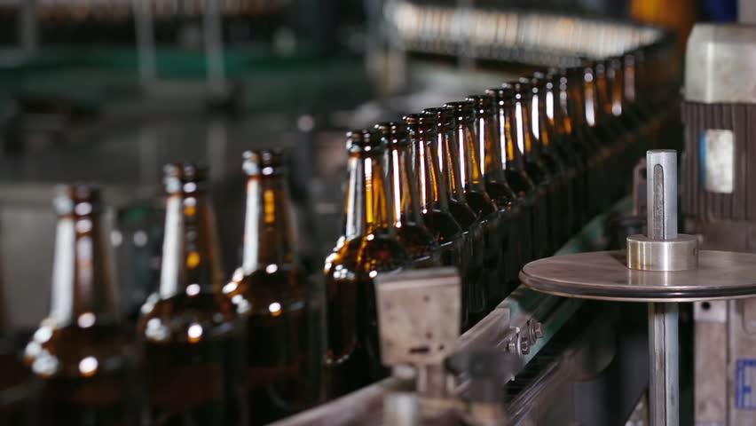 Technological line for bottling of beer in brewery. Empty brown bottles in a line in factory. Bottles Moving on Conveyor Belt at Glass Bottle Factory. Clean beer bottles are moving along the conveyor. | Shutterstock HD Video #1008979811
