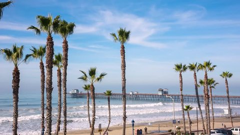 California Oceanside pier view over the ocean with palm trees and beach, travel destination