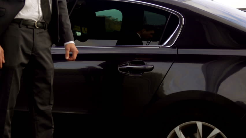 Personal driver is opening the car door for his client, hotel transfer services