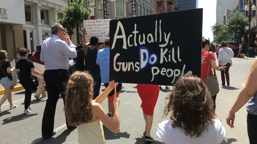 "NEW OLREANS, LOUISIANA CIRCA MARCH 2018 - Two Children girls holding ""Guns Do Kill People"" sign in March for our lives demonstration"