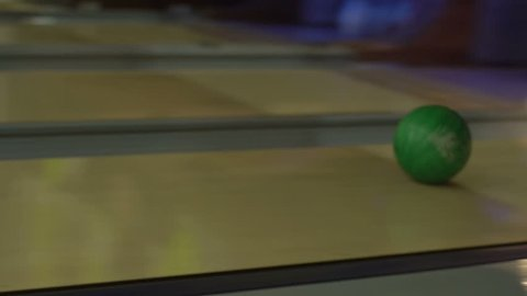 The woman is throwing the bowling ball. It is crashing into the skittles.
