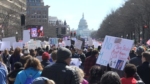 WASHINGTON, DC - MAR. 24, 2018; With Trump International Hotel within shouting distance, thousands of demonstrators  arrive March for Our Lives Pennsylvania Avenue. Pan to hotel.