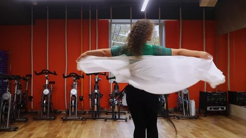 Woman dances with white cloth near bicycle trainers in gym of sports club