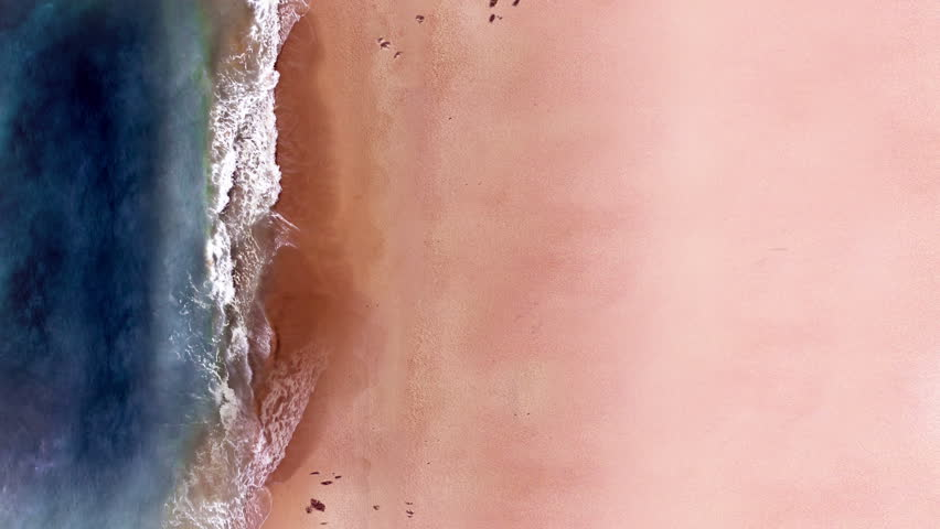 Top view of sand beach and sea side. Looping ocean surface texture, Aerial view sea waves slow motion, flying over tropical sandy beach and waves, Sunset  beach seamles loop.  | Shutterstock HD Video #1009050941