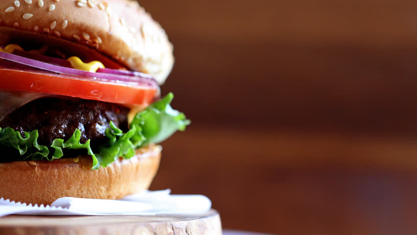 Grilled real American beef burger with lettuce, tomato, onion and mustard served on pieces of brown paper rotating on a rustic wooden counter. Close-up of burger with copyspace on wooden texture | Shutterstock HD Video #1009078601