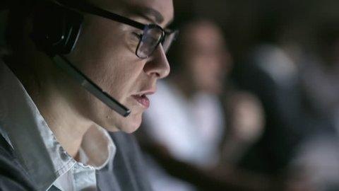PAN of female helpline agent in glasses talking on headset