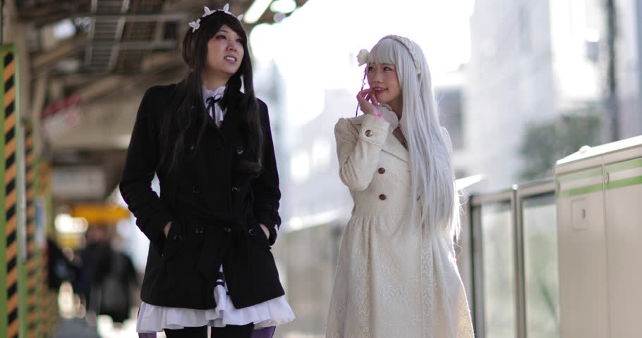 Japanese female friends in train station, Harajuku, Tokyo, Japan
