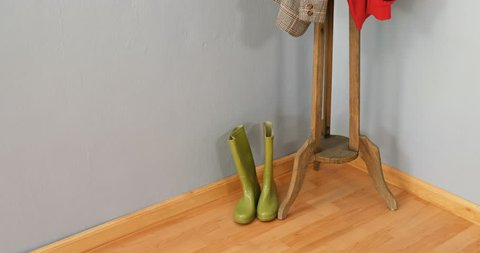 Warm clothes, umbrella, and wellington boots arranged on wooden stand 4k