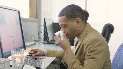 Business man coughing and sneezing in a small office