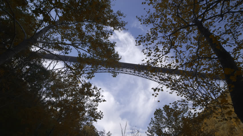 Cinematic tracking shot from under New River Gorge Bridge near Fayetteville in West Virginia shot in fall with autumn color & blue sky & white clouds demonstrating the steel structures immense size.