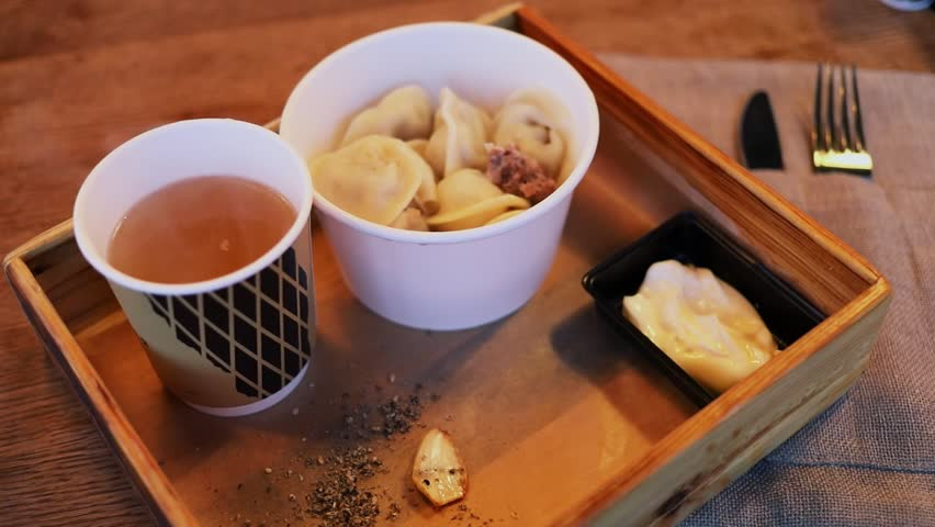 Hot tea and russian meal pelmeni are in wooden box on table
