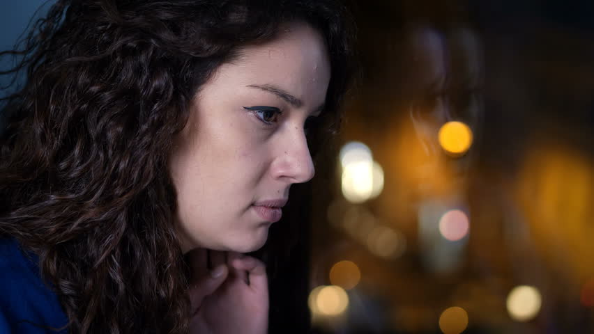 Sad and depressed young woman at the window at night | Shutterstock HD Video #1009155821