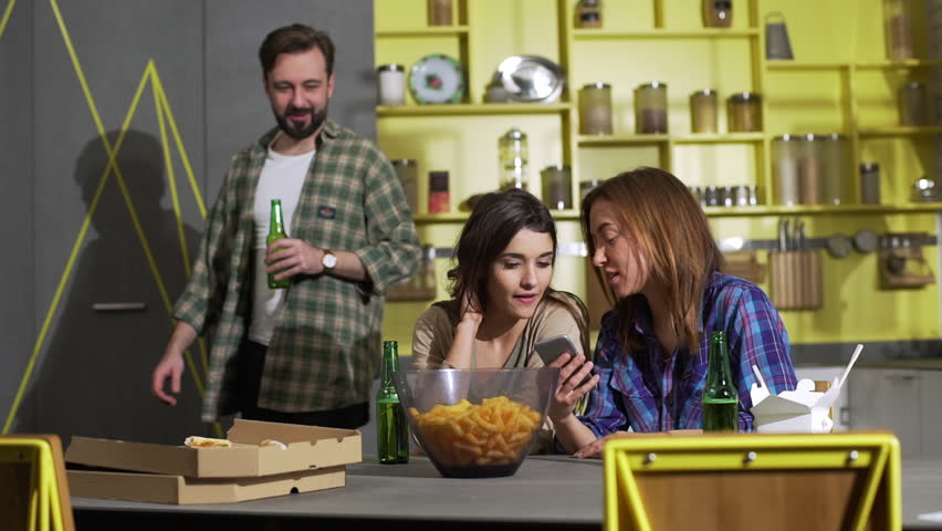 Portrait of modern young friends man and women resting at home in weekend, eating and drinking beer while discussing news from internet slow motion   Shutterstock HD Video #1009163111