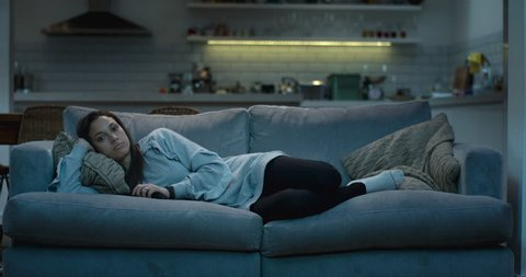 Young woman lying down on a comfy sofa at night watching the television