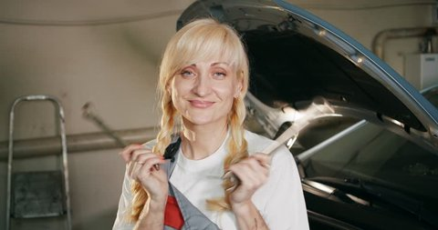Portrait of a blonde female mechanic repairing a car in a garage workshop. Car maintenance concept.