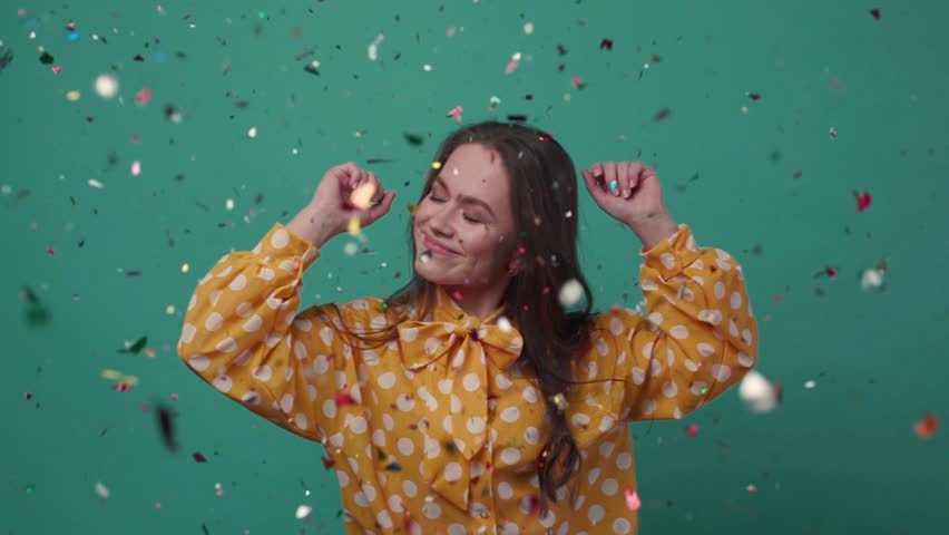 Beautiful young woman dances alone in colorful confetti on a green background.